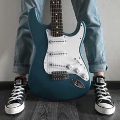Suki stood up against the wall, her blue, electric guitar in between her legs…