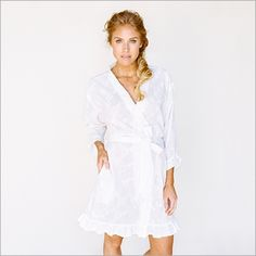 <p>Sweet ruffles and cotton embroidery bloom across this knee length robe. This pretty cotton robe evokes a shabby chic, vintage feeling and features petite ruffles at the hem and each sleeve.</p> <ul> <li>Includes sash and inner ties.</li> <li>100% cotton</li> </ul>