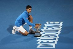 Novak Djokovic of Serbia holds the Norman Brookes Challenge Cup after winning his men's final match as Andy Murray of Great Britain looks on during day 14 of the 2015 Australian Open at Melbourne Park on February 1, 2015 in Melbourne, Australia