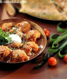 Malai Kofta Curry: Homemade dumplings of paneer (homemade Indian cheese) mixed with cashews & raisins, dipped in chickpea batter, lightly fried & cooked in a rich creamy sauce.