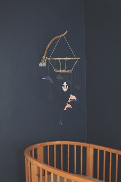diy mobile from felt and drift wood- love the flag pole holder on the wall for the wood!