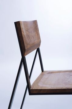 In profile, it looks to be a slender, linear chair, but when turned you notice the shape made from solid steel and wooden back and seat elements.