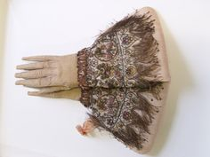 The Worshipful Company of Glovers of London - rly pair of embroidered gloves with long extended fingers, circa 1595 - 1605, of white leather dyed buff, suede side uppermost, separately worked deep and wide gauntlets, each with nine shallow scalloped shaped tabs edged in long fringes terminating in sequins, each worked in silks and metal threads with assorted fruit or flowerheads, the main panel with delicately coiling gold strip tendrils enclosing phoenix rising from the flames.  37cm long.