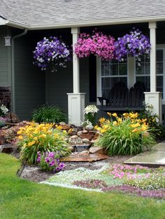 DIY front landscaping with pondless waterfall. A mixture of perennial and annual flowers keep the flowerbed looking lush all summer and is an inexpensive way to add curb appeal (tip: install a drip line for the hanging baskets - much easier than hand watering!) The black adironack style front porch swing that we built serves as the perfect place to sip lemonade
