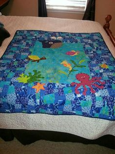 Under the Sea Baby Quilt for Baby Kevin. This is a crazy nine-patch with sea animals appliqué. I made the center a solid piece of fabric so that the animals would be more visible.