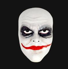 Venetian mask inspired by Heath Ledger's iconic role as the Joker from the Dark Knight. The white mask has been created in Venice using a papier mache base and then hand painted and decorated.The mask secures with ribbon ties.