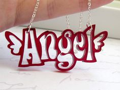 """This necklace features the word - """"angel"""" (2.3"""" ,or 57mm) made of Translucent Red acrylic. It comes on a silver plated delicate Cable Chain.     The necklace measure approx: 17"""" (43cm).     If you need a different length please let me know in the """"message to seller"""" section of the checkout process .     All of my jewelry comes with a gift box.  Price: $27"""