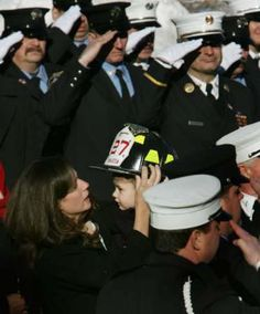 Son has lost his dad but wears his helmet. Eileen Bellew (botom-L) wife of fallen New York City firefighter John G. Bellew, places Bellews helmet on their three-year-old son Jacks head as members of the FDNY salute outside St. Margarets of Antioch Roman Catholic Church in Pearl River, New York, January 27, 2005, following Bellews funeral.