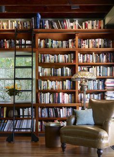 Library wall: At one end of a large living room in this 19th century renovated carriage house, a bookshelf wall helps define and organize a cozy office space.