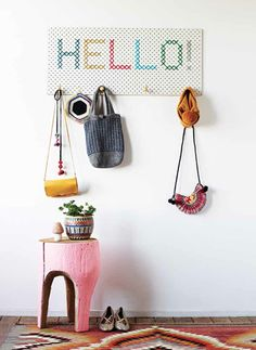 A cross stitch greeting turns a pegboard into a welcome center near the front door or in the mud room.