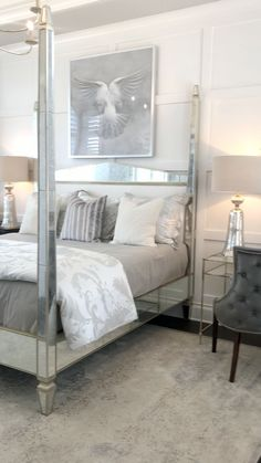 Modern Glam style in this owners suite is created by the four poster mirrored bed, glass desk as a nightstand, wall trim, luxe bedding & seating area. Taken while touring a model home for design inspi Master Bedroom Interior, Glam Bedroom, Woman Bedroom, Modern Bedroom, Ikea Bedroom, Hotel Inspired Bedroom, Glam Bedding, Bedroom Mirrors, Mirrored Bedroom Furniture