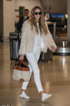 Off-duty glamour! The Australian personality flaunted her trim legs in tight white jeans, while adding bulk to her slender upper half by donning a furry jacket and white T-shirt