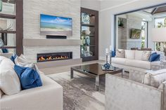 727 Buttonbush Lane, Naples, FL 34108 | Coastal contemporary living room with fireplace, wall of glass that opens completely to the outside and European oak wood floors.  Pelican Bay