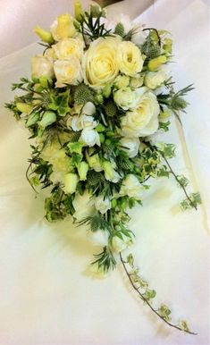 A bridal bouquet of white Rose, Lisianthus, Freesia, Thistle, Rosemary and Ivy #weddings #flowers #florist #BridalBouquet #TrailingIvy