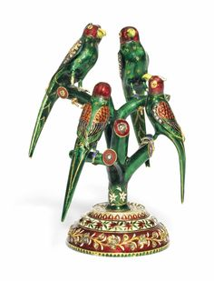A GROUP OF GEMSET AND ENAMELLED GOLD PARROTS NORTH INDIA, 19TH CENTURY Each of the four birds with long tails, green bodies, red heads, and ruby-set eyes, two of the parrots with extended combs, each bird perched on a branch of a tree with a diamond-set end, one side of the tree trunk with a band of scrolling floral vine, the stepped conical base with bands of scrolling floral vine, the lower band with inset diamond-set vine, the underside of the base with a plain gold plaque 5¼in. (13.2cm.)…