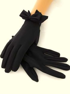 Black double bow wrist length gloves. If wearing an evening dress, a pair of very long black gloves are the most elegant. The correct glove etiquette for the length of glove is dependant on the length of your sleeve – the shorter the sleeve, the longer the glove and therefore opera gloves are properly worn with sleeveless or short-sleeved dresses/evening gowns.