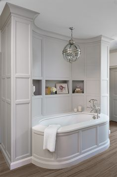 Incredible master bathroom with oval gray paneled bathtub filling built-in gray paneled nook accented with bookshelf illuminated by Restoration Hardware chandelier.