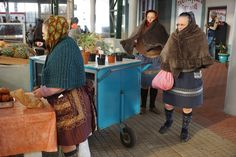 The ladies are shopping for food at the local market,.