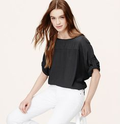 Finished with cool button tab sleeves, we heart the drapey ease of this dolman style. Boatneck. Short dolman sleeves. Front yoke. Roll cuffs with button tabs.