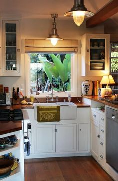This cozy, charming kitchen features beautiful wood on the counters and floors as well as a window that gives you great outdoor views, making you feel like you're doing dishes in nature. Check out more of this retreat-like home on ApartmentTherapy.com