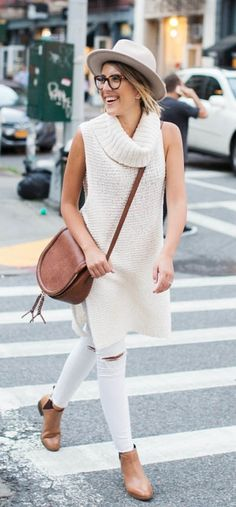 A sleeveless sweater, and white distressed jeans