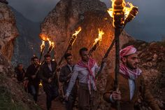 Kurdish men wearing traditional clothing and carrying flaming torches arrive at the top of a mountain overlooking Akre. This is the culmination of the day's festivities. [John Beck/Al Jazeera]
