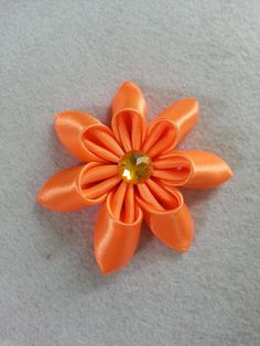 Make beautiful flowers for your craft projects. This flower will make a lovely wedding bouquet, brighten up your scrapbook, make beautiful hair accessories, etc..    Materials   satin ribbon felt gem needle thread fabric glue scissors