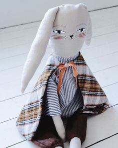 "Alex the Bunny is one of the many friends who will be in the shop tomorrow at 12 noon. Alex loves putting on magic shows and playing in blanket forts. He's the perfect cuddle size at 26"" long. He wears a seersucker blue and white striped shirt with brown linen harem pants and a snuggly, reversible flannel plaid cape. He's hand sewn with a hand painted face. Use code MERMAGfriday for free shipping tomorrow only.  @merrileeliddiardshop #mermagdolls"
