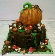 A nature cake with a big pumpkin, smaller pumpkins and small mushrooms