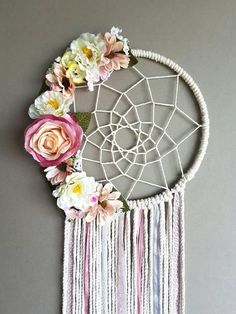 Pink and white dreamcatcher. This beautiful wall hanging is made with beige string pink and white ribbon for, pink and white florals attached for that girly touch, intricate webbed detail, ready to give you that perfect dreamy night sleep. Size approx 10inch 25cm hoop 33inch/84cm long