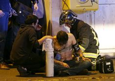 French fire brigade members aid an injured individual near the Bataclan concert hall following fatal shootings in Paris on November 13, 2015.