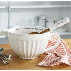 2-piece set.  Fluted ceramic mixing bowl features debossed 'Bake the world a batter place' message.  Comes with debossed 'BATTER UP' wood mixing spoon with stamped ceramic handle.
