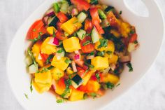Easy Cucumber Mango Salsa with cucumber, jalapeno, mango and other veggies. Sweet with spicy that'll make a great topping to any dish!
