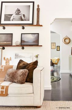 Leaning art on shelves in living room with neutral pillows on sofa