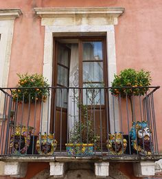 Taormina, Sicily - A room with a view. Just one of the many cute balconies hanging over the narrow streets lined with souvenir, ceramic and fabric shops.