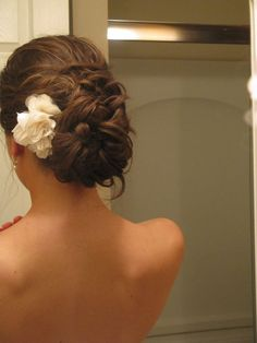 Woven low updo with hair flower.