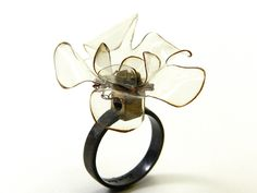 Ring   Ligia Roche.   Silver and recycled brass from an electrical outlet, with it's corresponding screw, a crochet rosette made with recycled copper wire from an electrical inductor. The plastic flower was molded with a lighter.