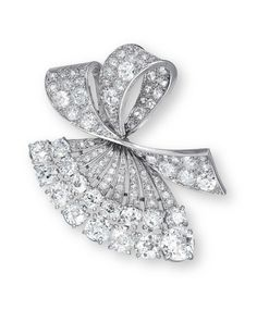 A DIAMOND BROOCH, BY BOUCHERON  Of folded ribbon design, set throughout with old mine and European-cut diamonds, mounted in platinum and 18k white gold, 5.0 cm long, with French assay marks for platinum and gold, in purple Boucheron case  Signed Boucheron