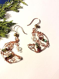 Crescent moon earrings with a Christmas touch , made in Copper Wire with red and green agate beads and gold hematite beads The ear hooks are also copper wire with a gold hematite bead. Drop length little over Moon diameter Green Copper, Green Agate, Red Green, Christmas Earrings, Christmas Jewelry, Moon Earrings, Copper Earrings, Wire Wrapped Jewelry, Wire Jewelry