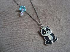 colar em metal, na cor prata, com pingente de panda em metal e esmalte preto e pingente de florzinha em cerâmica plástica verde menta e miçangas em tons de lilás. R$29,00