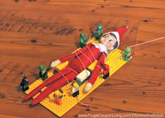 Funny Elf on the Shelf Ideas –  Elf is Captured by LEGOs. This idea, plus NEW Daily Ideas and dozens of FREE Christmas Printalbes for your Elf on Frugal Coupon Living. LEGO Elf on the Shelf Idea.