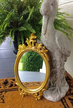 This is a beautiful gold ornate oval mirror. Made by Dart, a Syroco product made in the USA, 1977. Made of a sturdy plastic composite. In very good vintage condition both frame & mirror ( no scratches on mirror). Great size for bedroom, baby nursery, wedding decor, or wall statement decor. Hook on back for hanging!  Measures total 18.75 height X 10.5 wide, mirror 11 X 8.5  Thanks for shopping YellowHouseDecor!  Please visit my sisters shop for more vintage items ( ellansrelics02)