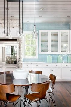 Light blue subway tile... not sure. The kitchen feels like a cupcake bakery or something, transitioning sharply into the hard, industrial brick and the modern lighting, table and chairs. I kind of like it, but it's also jarring.