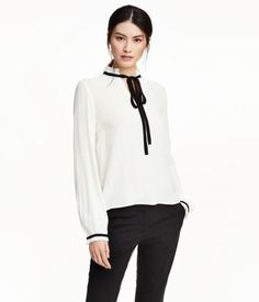V-neck blouse in airy woven fabric. Low stand-up collar with ruffle trim and contrasting tie, and long sleeves with fastener and narrow ruffle at cuffs.