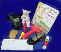 """Book """"If You Give a Pig a Pancake"""" and assortment of objects (shoe, hammer, etc.) for visually impaired"""