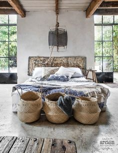"""New Ways to Style Your Bed's """"End Zone"""" Photographer and stylist Paulina Arcklin uses a trio of woven baskets at the end of the bed to add style and a place to store throws and pillows."""