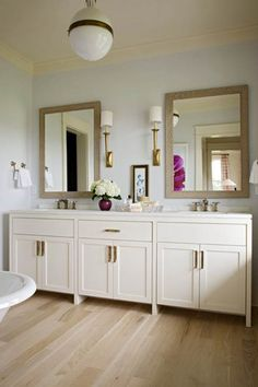 bathroom, master bath, gold sconces, white cabinets, light wood floors, gold hardware