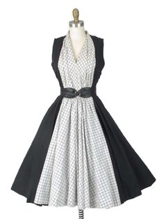authentic 1950s black swing dress with ivory and black windowpane check colorblocking down center of dress. A fabulous retro look for a dance, rockabilly event or wherever you want to standout! Red accessories would complement it nicely.<br /><br />DETAILS<br />•Fitted sleeveless V neck bodice.<br />•Standup collar at back neck.<br />•Pleat on both sides of neck continue down bodice front.<b...