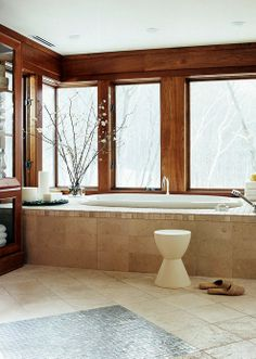 With an upper-level perch and a wooded location, this serene bathroom is free from privacy concerns.  Candles on a rock-filled tray add a romantic feeling.  Flowering quince branches in a glass vase. Organic materials, such as custom cherry woodwork and tumbled-marble tiles, further merge indoors and outdoors. Clear canisters in the tall towel cabinet create simple, elegant storage.