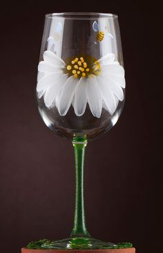 Designed by Pat Barker, a New England artist, this hand painted wine glass is adorned with two large daisies and two buzzing bees sure to make